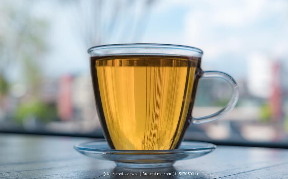 Gelber Tee in einer Glastasse